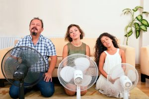 family of 3 sitting in living room in front of fans to cool off