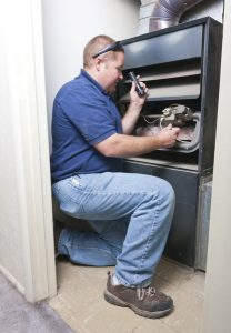 technician checking the inside of a furnace