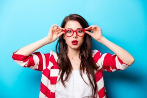 beautiful surprised young woman in glasses standing in front of wonderful blue background