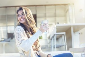 woman-smiling-with-glass-of-water-in-her-hand