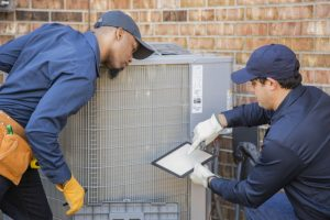 two-technicians-looking-over-checklist-as-they-service-air-conditioner