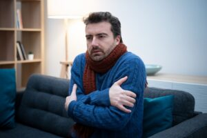 man-huddled-on-couch-with-sweater-and-scarf-looking-cold