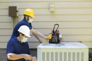 two-technicians-working-on-air-conditioner-outside-unit